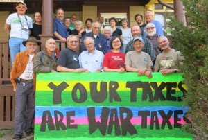 """Conference attendees posing behind a large sign that reads """"Your Taxes are War Taxes"""""""