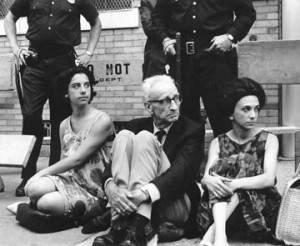 A.J. Muste and two other protesters sit with police standing behind them