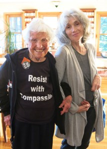 Frances Crowe wearing a shirt that says Resist with Compassion, links arms with Susan Lannen