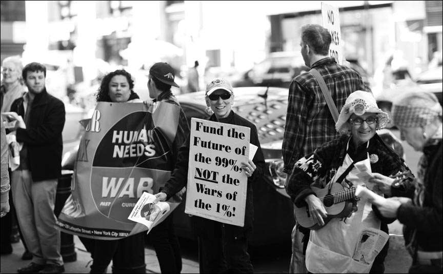 """amid other protesters, Ruth Benn holds sign reading """"Fund the future of the 99%, not the wars of the 1%!"""""""