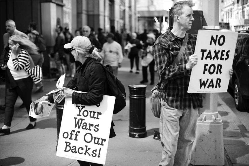 "Two people on crowded sidewalk holding signs reading ""[Get] Your Wars off Our Backs!"" and ""No taxes for war"""