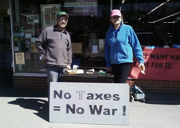 "Two people staff a penny poll table over a sign reading ""No Taxes = No War!"""