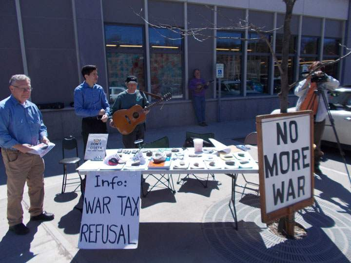 "man with guitar behind a literature table with two large signs before it reading ""Info: war tax refusal"" and ""no more war"""