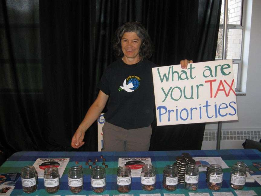 """woman standing behind penny poll table holding a sign that reads """"what are your tax priorities"""""""