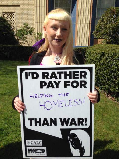 "Woman holds sign reading ""I'd rather pay for helping the homeless than war!"""