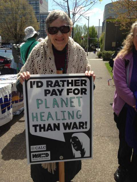 "Woman holds sign reading ""I'd rather pay for planet healing than war!"""