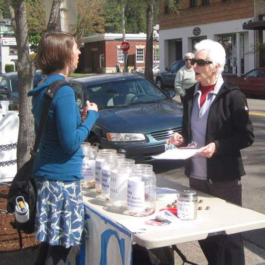 two women interact across penny poll table