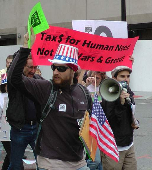 "man in Uncle Sam hat holding American flag marching in front of banner reading ""Tax $ for Human Need, not [for] Wars & Greed"""