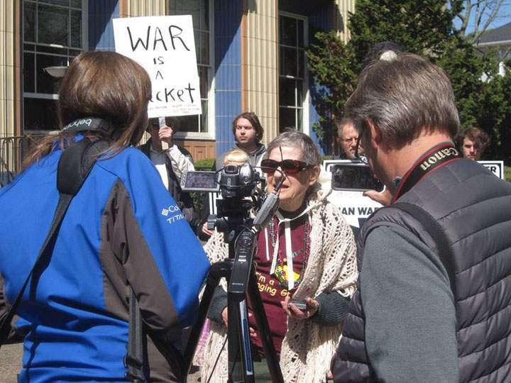 "woman facing camera speaks into microphone, man holds sign in the background that reads ""war is a racket"""