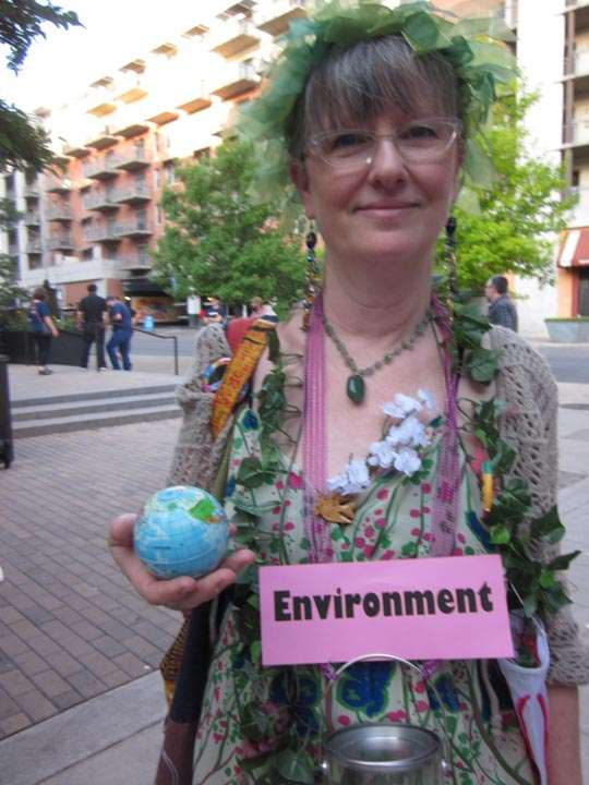 "Woman wearing garlands, holding globe, labeled ""Environment"""