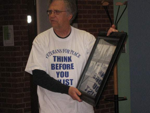 "Mike Hastie holding display case, wearing a t-shirt that reads ""Veterans for Peace: Think before you enlist"""