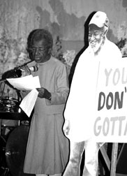 "Juanita speaking next to an image of her partner Wally with a sign saying ""You Don't Gotta"""