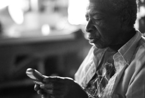 black and white photo of Juanita Nelson using a cell phone. photo by Ed Hedemann