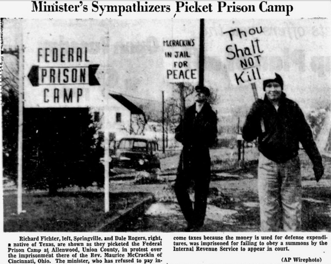 Richard Fichter, left, Springville, and Dale Rogers, right, a native of Texas, are shown as they picketed the Federal Prison Camp at Allenwood, Union County, in protest over the imprisonment there of the Rev. Maurice McCrackin of Cincinnati, Ohio. The minister, who has refused to pay income taxes because the money is used for defense expenditures, was imprisoned for failing to obey a summons by the Internal Revenue Service to appear in court.