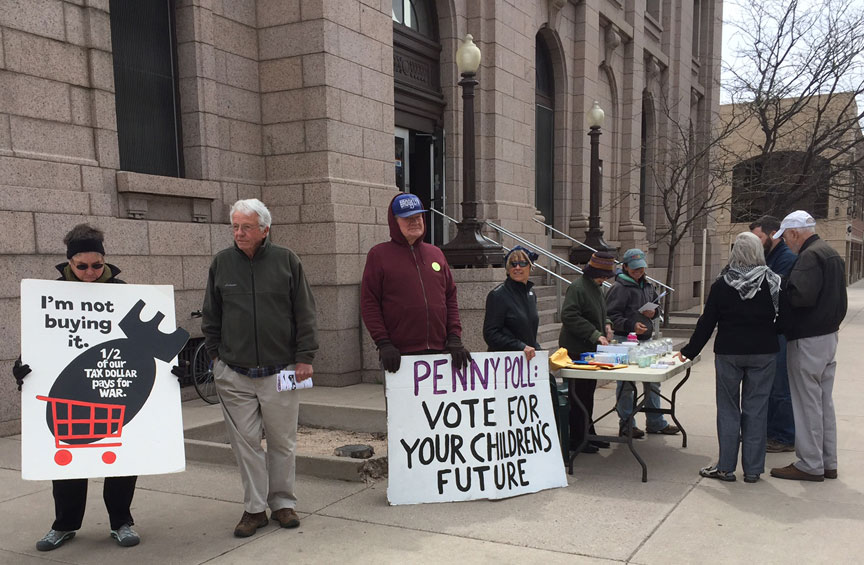 Members of the Bijou Community attracted attention with signs and a penny poll outside the post office in Colorado Springs. Photo by Donna Johnson.