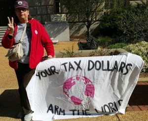 "Carol Coney flashes peace sign next to banner reading ""your tax dollars arm the world"""