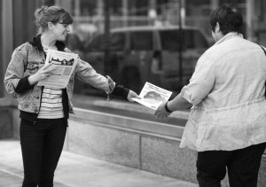 activist hands a War Resisters League federal budget pie chart to a passer-by