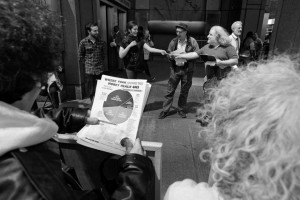 person holds War Resisters League federal budget pie chart in foreground while redirection ceremony is taking place in the background