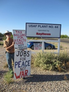 "man holding signs reading ""tax dollars for health care not missiles"" and ""jobs for peace not war"" in front of a sign reading ""U.S.A.F. plant #44, operated by Raytheon"""