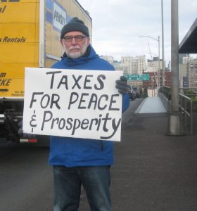 John Grueschow spreads the message of the Portland war tax redirection.