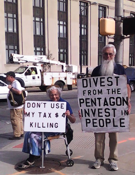 "two people holding signs on the sidewalk: ""Don't use my tax money for killing"" and ""Divest from the Pentagon; invest in people."""