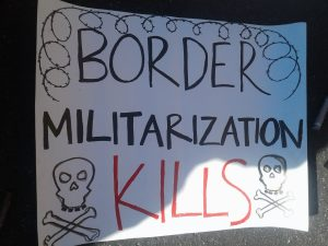 "white sign with skull and crossbones and barbed wire, saying in black and red text: ""BORDER MILITARIZATION KILLS"""