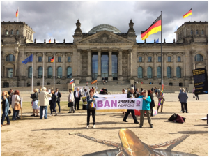 "A protest in front of the Reichstag - two people hold a banner reading ""BAN URANIUM WEAPONS"" in front of a scattered group of about 40 people."
