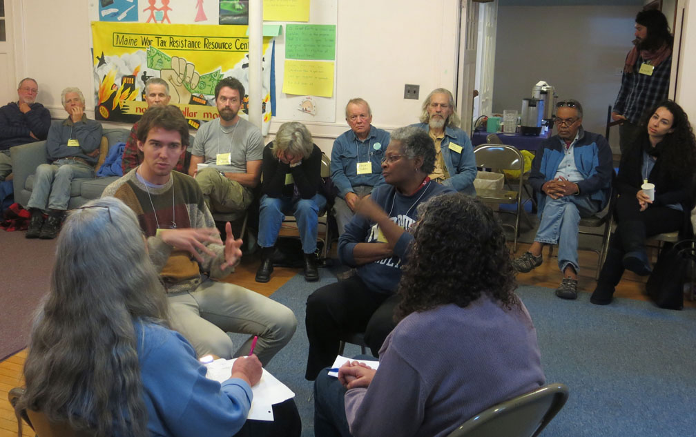 A fish bowl exercise at the New Englanf GAthering. Pictured are NWTRCC field organizer Sam Koplinka-Loehr speaking, and (clockwise) Mandy Carter, Mary Regan, and Joanne Sheehan with backs to camera. Photo by Ruth Benn