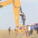 "A man, ""Happi"" American Horse, is shown standing atop the shovel of an excavator in a field. People and cars in the background."