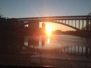 Photo of a sunrise over a body of water. A bridge span appears to be over the top of the sunrise.