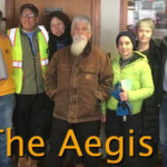 "photo of nine people in winter clothes standing in a row indoors facing the camera, with the words ""The Aegis 9"" at the bottom of the photo"
