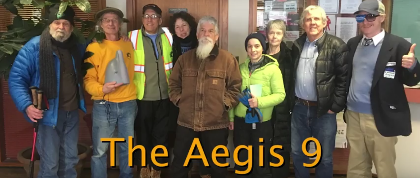 "photo of nine people in winter clothes standing in a row indoors facing the camera. with the words ""The Aegis 9"" at the bottom of the photo."