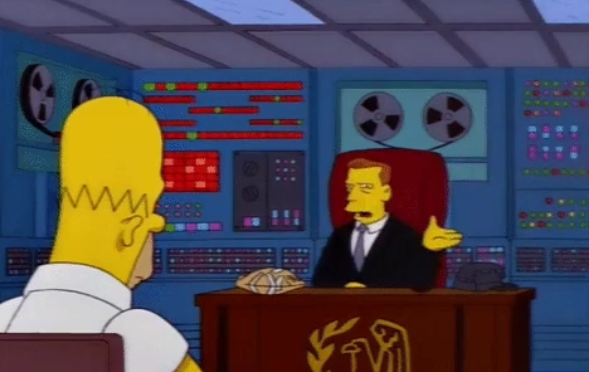 Homer Simpson sits in front of an IRS agent at a desk, with an old supercomputer on the wall behind the agent