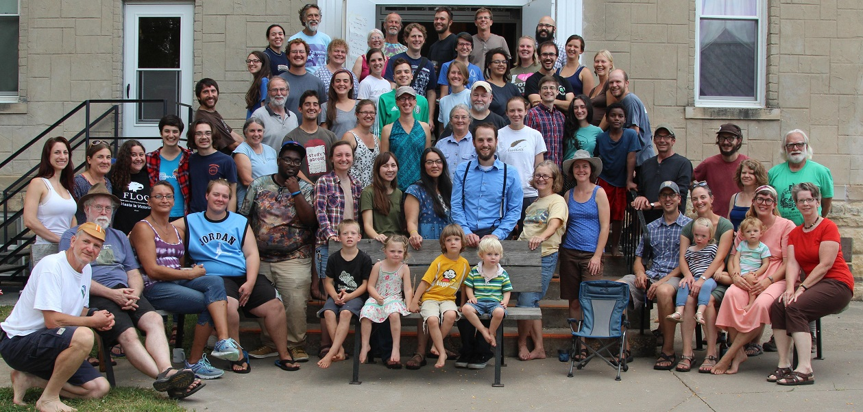 group photo with four small children sitting on a bench in front of a group of over 50 adults standing on porch stairs