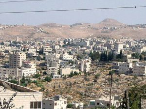 a photo of desert hills in the distance with Beit Sahour, composed of many white short and medium sized buildings in the middle and foreground