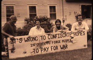 "sepia-toned photograph of kneeling resisters in Colrain with a large horizontal sign reading ""It's wrong to confiscate homes in order to force people to pay for war"""