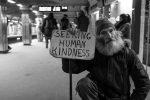 "Man holding a sign reading""Seeking Human Kindness """