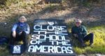 Close the School of the Americas banner with woman and man on both sides