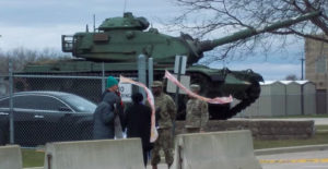 US Army tank in the background with military personnel and people with banners in front