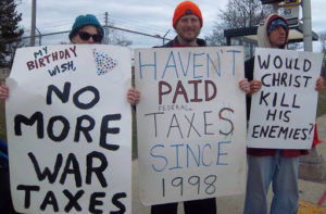 3 people holding signs stating opposition to paying taxes for war