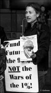 "woman holding a sign that reads ""Funding the future of the 99% NOT the wars of the 1%"
