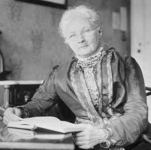 woman sitting at a table with an open book looking at the camera