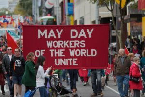 People in the street around a banner that states MAY DAY Worker of the world unite