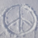 Image of a peace sign drawn in white sand