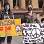 two people holding signs and wearing masks