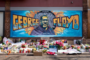 mural on the side of building with flowers and objects placed on ground as a memorial