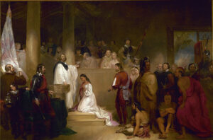 Gathering of 30 people who are surrounding a woman in white kneeling in front of a man in white who appears to be speaking to the crowd