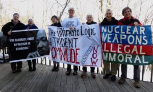 7 people holding signs smiling