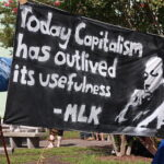black banner held outside that reads 'Today capitalism has outlived its usefulness'