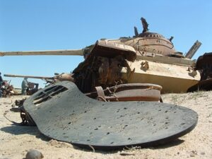 Sole of shoe in forefront with a tank in desert in background